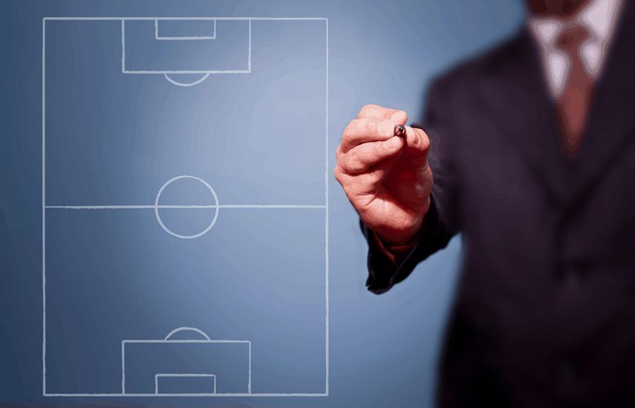 Das Bild zeigt einen Mann im Anzug, der mit einem Stift auf eine Wand mit einem Fußballfeld malt. Management und Profifußball