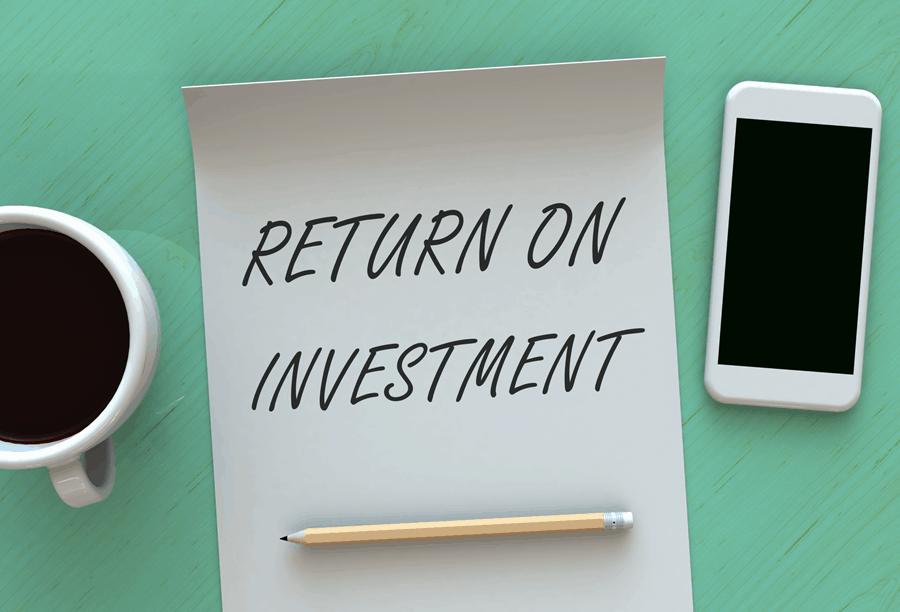 Das Bild zeigt den Begriff Return on Investment neben einer Tasse Kaffe und einem Smartphone.