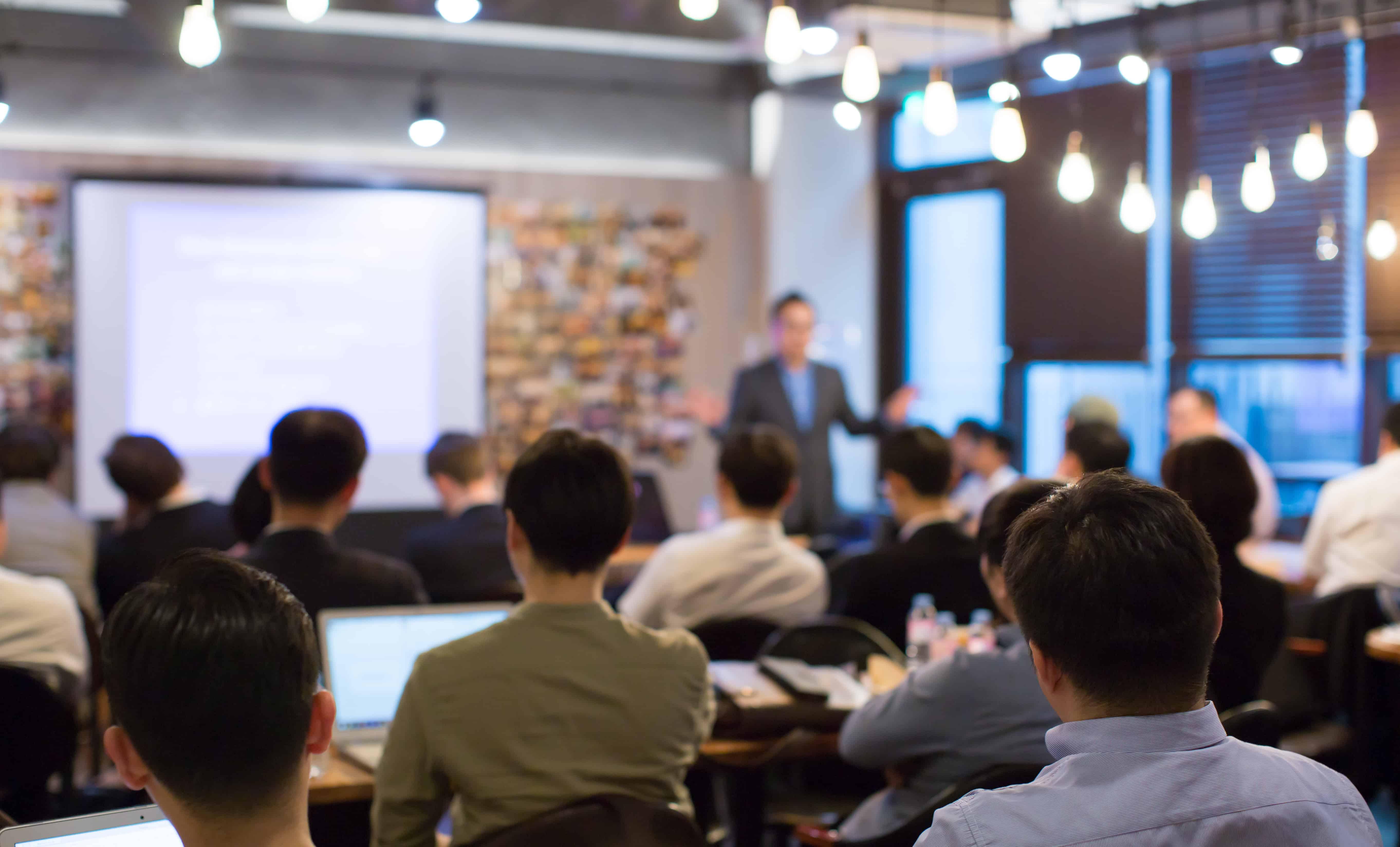 Das Bild zeigt einen Redner in einem Saal, das Bild ist verschwommen.