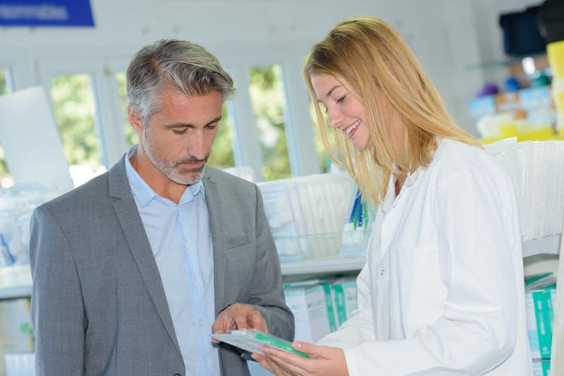 Ein Pharmavertriebsmitarbeiter erklärt einer Apothekerin ein Produkt